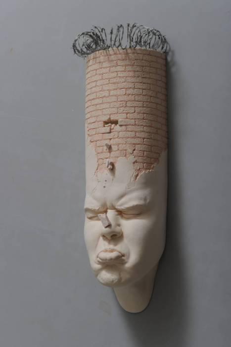 Голова человека, вытянутая вверх, и обнесенная колючей проволокой.