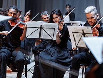 Музыканты симфонического оркестра с инструментами и нотами. Фото.